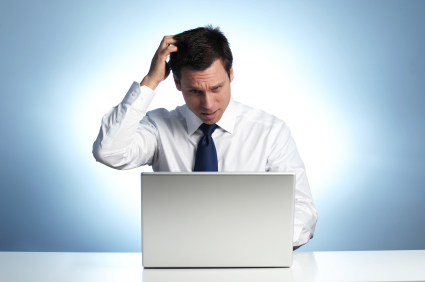 Businessman Scratching Head, with Laptop